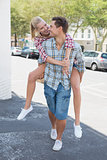 Young hip man giving his blonde girlfriend a piggy back