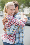 Couple in check shirts and denim hugging each other