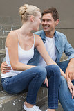 Hip young couple sitting on steps smiling at each other