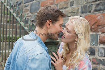 Hip young couple standing by railings about to kiss