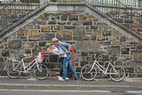 Hip young couple dancing by brick wall with their bikes