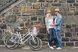 Hip young couple hugging by brick wall with their bikes