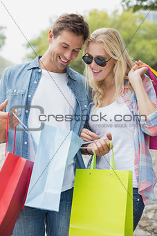 Hip young couple looking in shopping bags