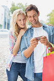 Hip young couple looking at smartphone on shopping trip