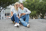 Hip young couple sitting on skateboard kissing