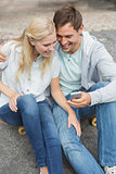 Hip young couple looking at smartphone sitting on skateboard