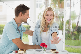 Hip young couple sitting at table admiring engagement ring