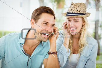Hip young couple listening to music together