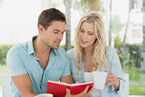 Hip young couple having coffee together reading book