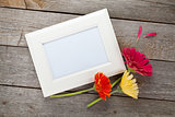Three colorful gerbera flowers and photo frame