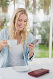 Pretty blonde sitting at table having coffee sending text