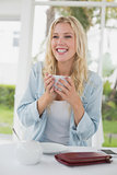 Pretty blonde sitting at table having coffee smiling at camera