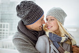 Cute couple in warm clothing smiling at each other