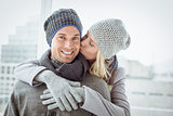 Cute couple in warm clothing hugging man smiling at camera