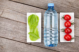 Green salad leaves, water bottle and tomatoes
