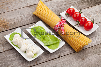 Tomatoes, mozzarella, pasta and green salad leaves
