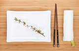 Empty plate, chopsticks and sakura branch