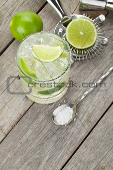 Classic margarita cocktail with salty rim on wooden table