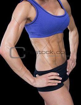 Female bodybuilder posing with hands on hips mid section