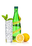 Glass of water with ice, bottle, measuring tape, lemon and mint