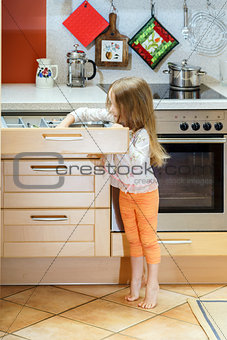 Little girl getting tableware before dinner
