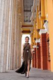 Girl in Greek style walking along marble columns