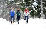 Three girls run on the forest path