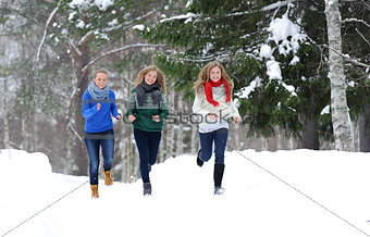 Three girls run on the forest path