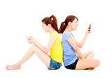 two happy pretty girls playing smart phone
