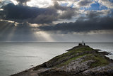 Lighthouse on headland with sun beams over ocean landscape with