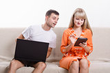guy with laptop sitting on couch, looking at tablet girl