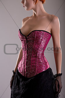 Close-up shot of elegant young woman in pink corset
