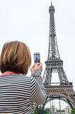 woman taking photographs of eiffel tower paris using a cellphone