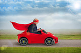 senior superhero driving a toy sports car