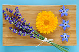 Summer herbs and edible flowers on wooden plate.