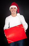 Smiling man in Santa hat gives a red box