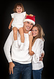 Father in santa hat holding little girl on his shoulder and hugg