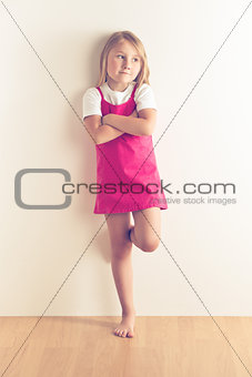 Little girl posing in front of a wall