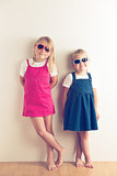 two little girls posing in front of a wall
