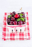 fresh red cherries on a white basket with check fabric