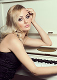 blond elegant girl near piano