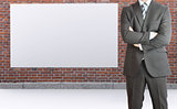 Businessman and brick wall with white placard