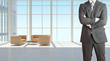 Businessman and large window in office building