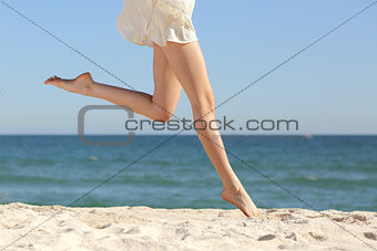 Beautiful woman long legs jumping on the beach