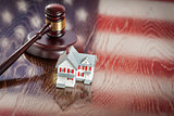 Small House and Gavel on Table with American Flag Reflection