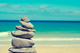 balanced stones in a white sand beach, with a cross-processed ef