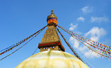 stupa with buddha eyes and prayer flags on clear blue sky