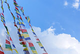 stupa with prayer flags on clear blue sky background