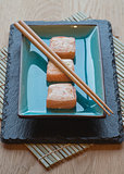 Fresh sushi salmon cream cheese parcels on plate with chopsticks