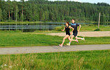Young couple running outside in summer in the nature